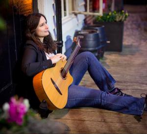 Edina Balczo sitting holding her spanish guitar
